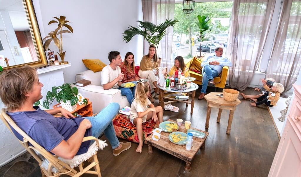 SLIEDRECHT - Lotte van den Herik heeft met haar zus een kledingwinkel in Sliedrecht.  Op zaterdagavond wordt er met de hele familie patat gegeten. Lotte zit op de bank en draagt een oranje/rode jurk. Haar echtgenoot aan haar rechterkant met flesje in de hand. COPYRIGHT DIRK HOL  (beeld DIRK HOL)