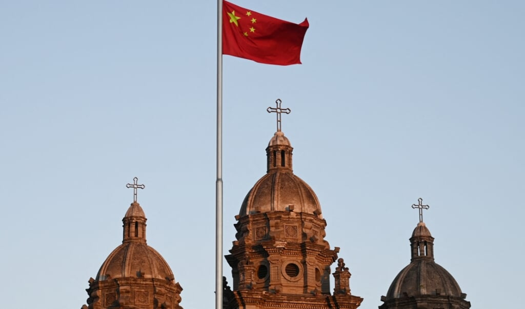 De Chinese vlag voor de Sint Jozefkerk in Beijing. Ondanks repressies groeit het (protestants) christendom in China.  (beeld afp / Greg Baker)