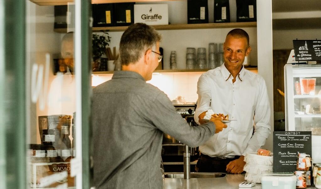 Dominee-barista Duurt Vonck serveert appeltaart aan een gast.  (beeld Judith Arendsen)