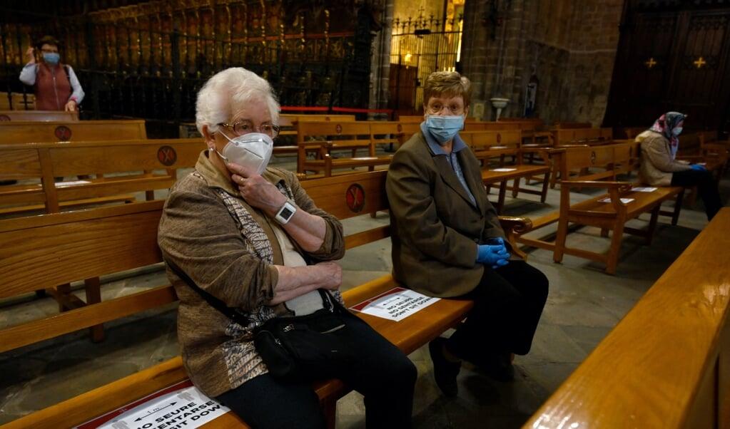 Afstand houden in de kerk.  (beeld afp / Lluis Gene)