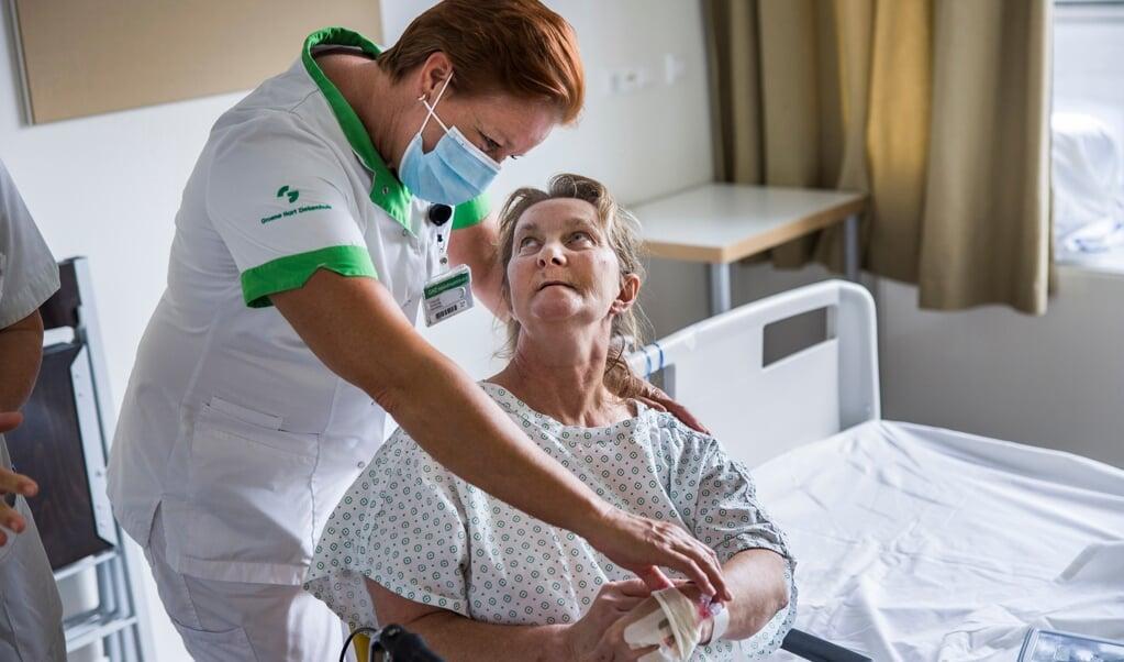 Verpleegkundige Carola Veer controleert een niet-gevaccineerde patiënt die kortgeleden van de intensive care is gekomen.  (beeld Arie Kievit)