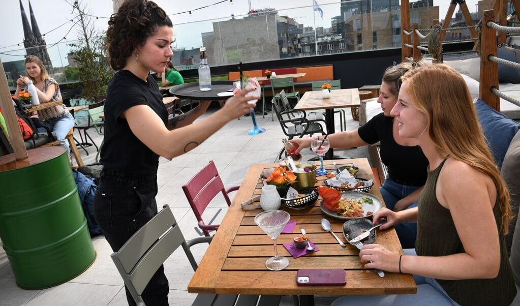 Gasten bij rooftopbar Doloris in Tilburg. De nieuwe maatregelen zijn voor niemand te handhaven, zeggen horecaondernemers.  (beeld Marcel van den Bergh)