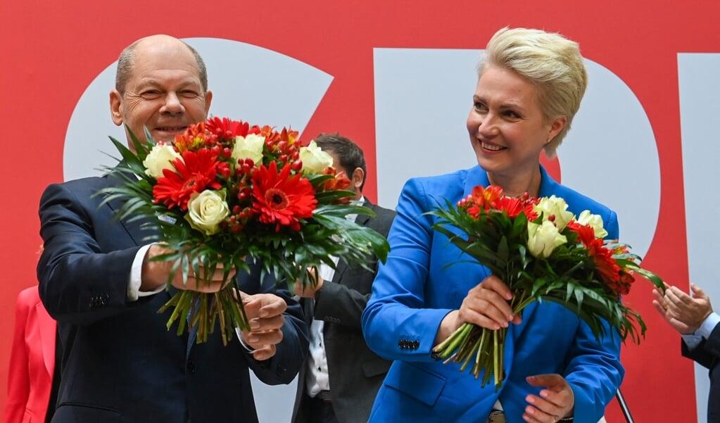 SPD-kanselierskandidaat Olaf Scholz en premier Manuela Schwesig van 'Meck-Pom' delen de bloemen.  (beeld afp / Christof Stache)