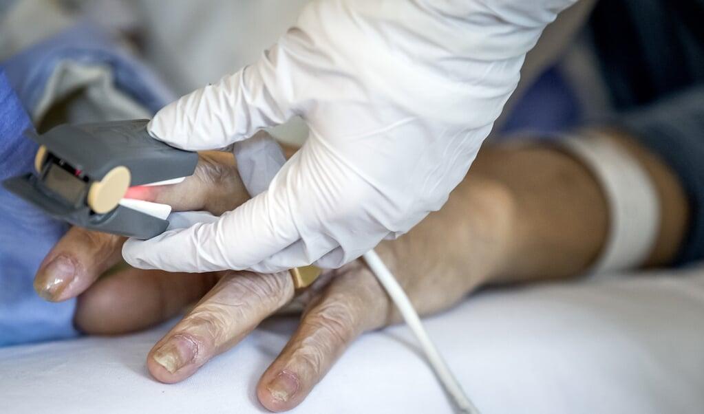 Een coronapatient op de covid-afdeling in het HMC Westeinde. Bijna een jaar na het begin van de coronacrisis is de zorg in het ziekenhuis nog niet terug naar normaal.   (beeld anp / Koen van Weel)