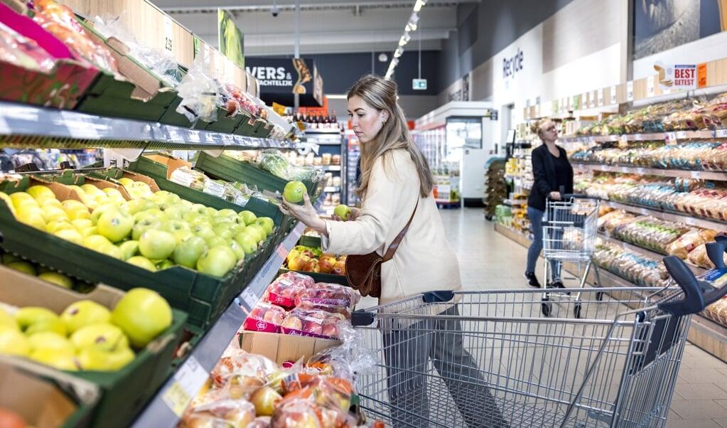 Een klant pakt een appel bij supermarkt Lidl.   (beeld anp / Ramon van Flymen)