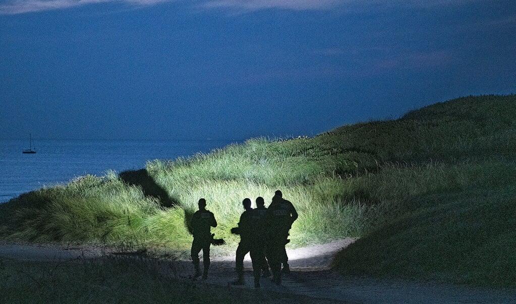 De Franse politie inspecteert de duinen bij Wimereux, waar het Kanaal op z'n smalst is. Veel vluchtelingen gaan via dit plaatsje naar Engeland met een bootje.  (beeld Guus Dubbelman)