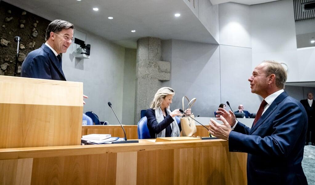 SGP-fractievoorzitter Kees van der Staaij (r.) heeft een onderonsje met demissionair premier Mark Rutte, op de tweede dag van de Algemene Politieke Beschouwingen. Op de achtergrond minister Kajsa Ollongren (Binnenlandse Zaken).  (beeld anp / Sem van der Wal)