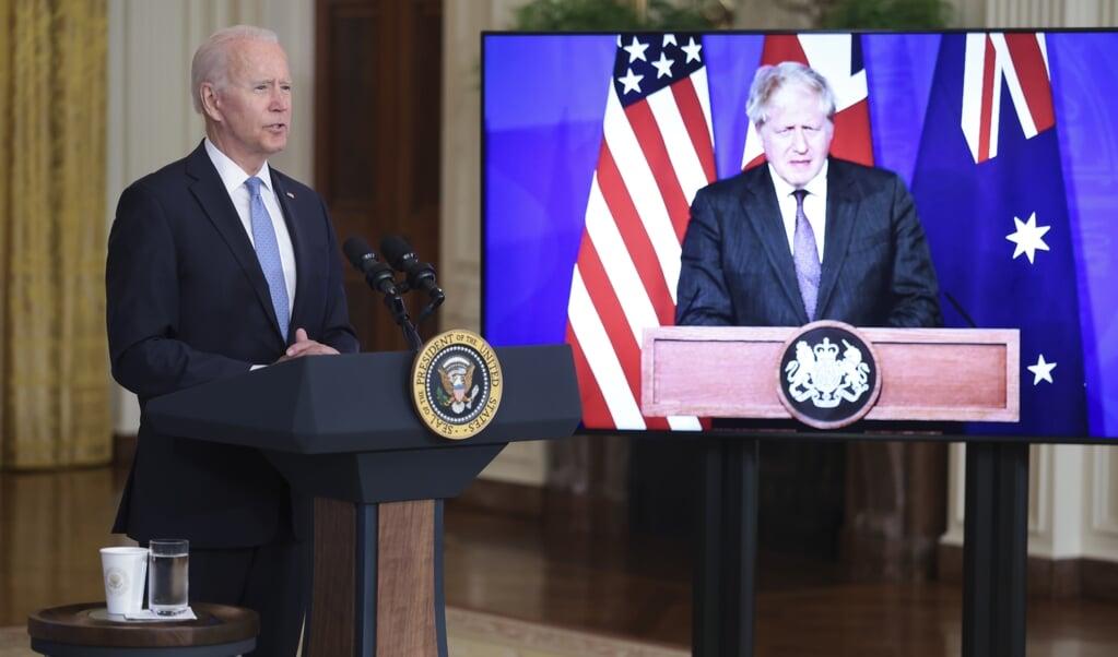 President Joe Biden (VS) presenteert 'AUKUS' virtueel, samen met Boris Johnson (VK) en Scott Morrison (Australië).   (beeld epa / Oliver Contreras)