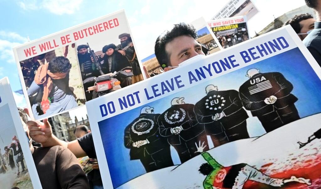 Voormalige Afghaanse tolken protesteren bij het Britse parlement.  (beeld afp / Glyn Kirk)