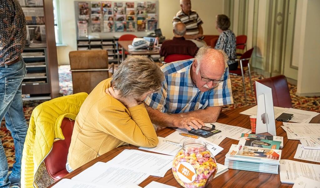 Vrijwilligers geven in de bibliotheek van Burgum aan ouderen uitleg over de QR-code en andere digitale onderwerpen.    (beeld Harry Cock)