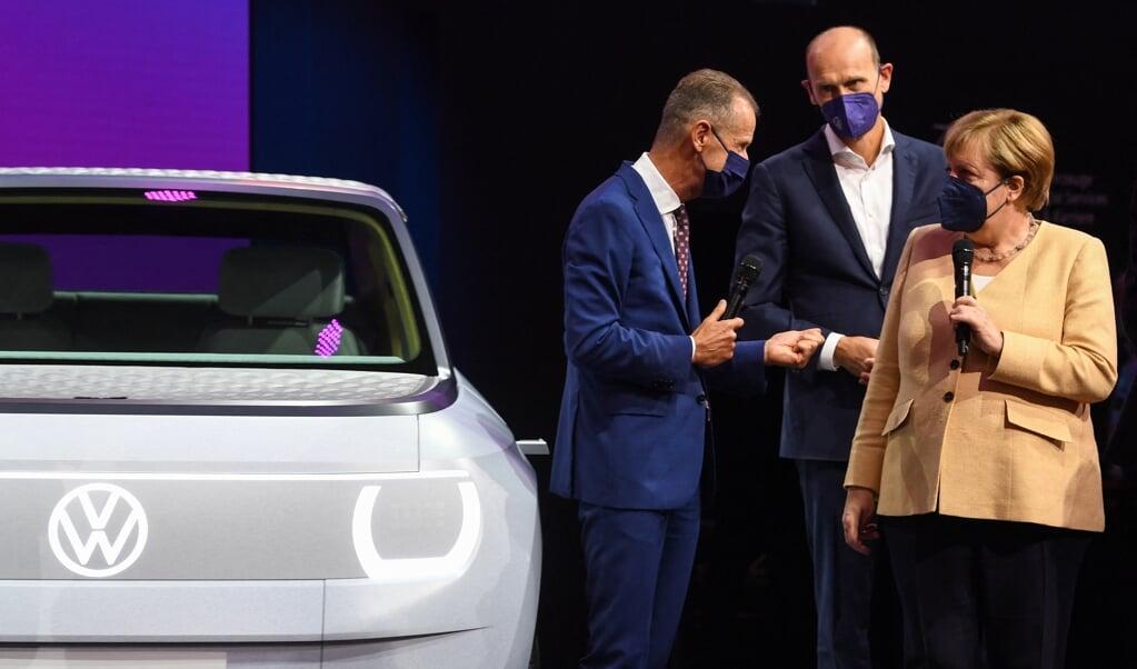 Angela Merkel praat met topman Herbert Diess van Volkswagen.  (beeld afp / Christof Stache)