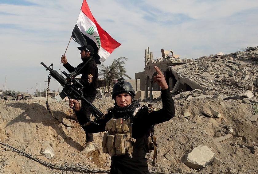 De Iraakse vlag wappert in Ramadi, 115 kilometer ten westen van Bagdad.  Volgens de Iraakse strijdkrachten is de stad sinds zondag weer vrijwel geheel onder controle, na een periode van bezetting door terreurgroep ISIS  (ap / Osama Sami)