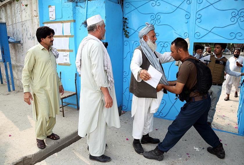 Afghaanse kiezers worden gefouilleerd, voordat zij hun stem mogen uitbrengen zaterdag bij de presidentsverkiezingen in Afghanistan.  Ondanks massale dreigingen van de taliban zijn zware aanslagen uitgebleven  (epa / Ghulamullah Habibi)