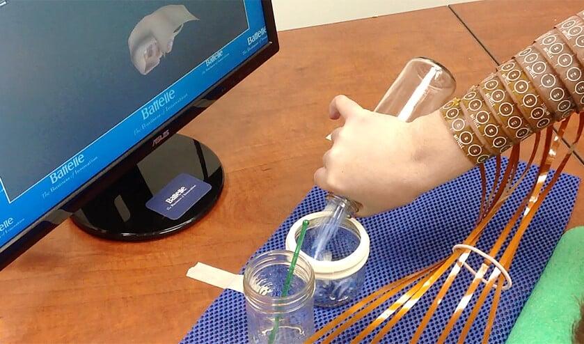 Ian Burkhart schenkt de inhoud van een kan over.  (Ohio State University, Wexner Medical Center)