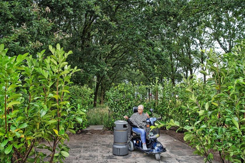 Een patiënt van het Meanderziekenhuis in Amersfoort op de nieuwe rookplek: een door bladeren gecamoufleerd hoekje. De oude rookplek, die in het zicht lag, is weggehaald.  (Guus Dubbelman)