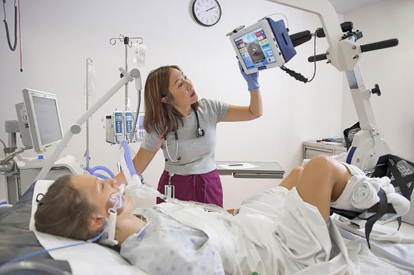 Een arts kijkt toe terwijl een IC-patiënt kilometers maakt met een speciale hometrainer.  (Marta Hewson)