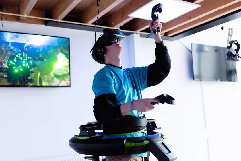 Een bezoeker van Virtuality in Amsterdam schiet op monsters in een game op de Virtuix Omni, een installatie voor virtual reality met ingebouwde loopband.  (Katja Poelwijk)