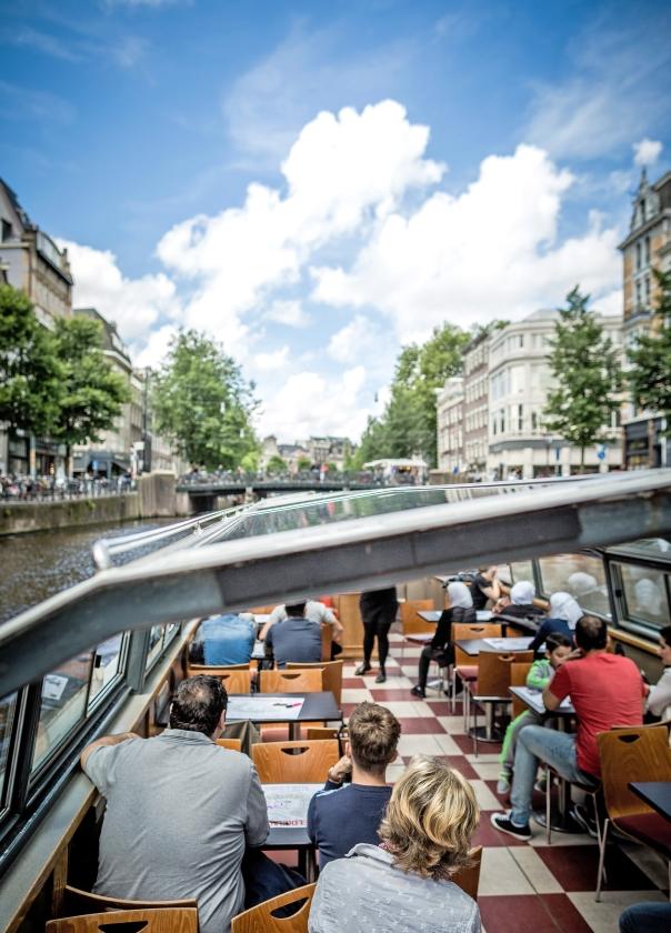 Vluchtelingen in Amsterdam maken een rondvaart, als onderdeel van hun inburgering.  (anp / Freek van den Bergh)