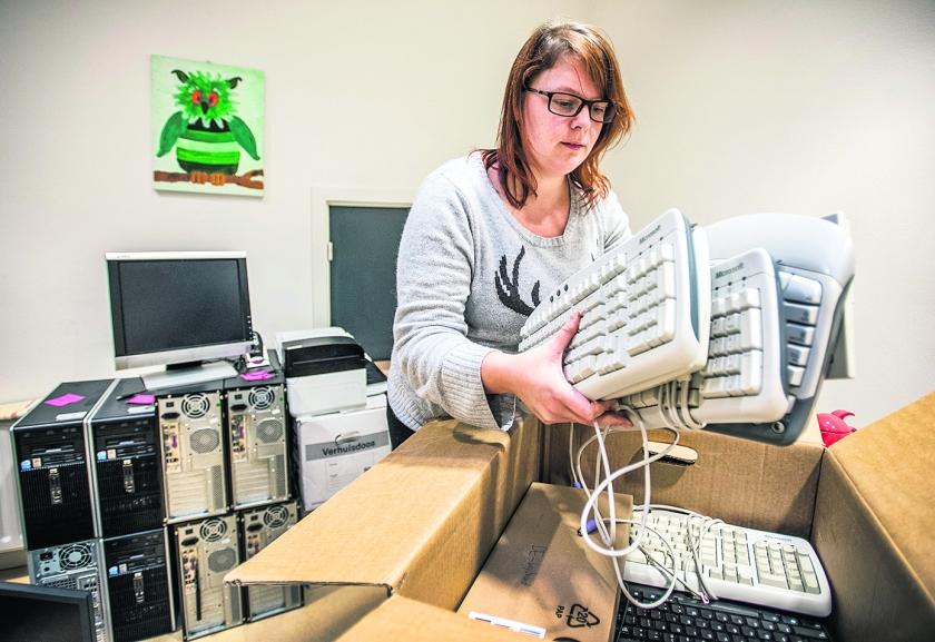 Hilde Lorier van Stichting Leergeld in Utrecht pakt een doos met toetsenborden uit voor haar cliënten.  (Raymond Rutting)