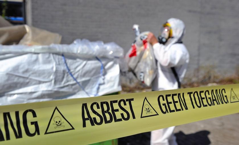Medewerkers van een asbestsaneringsbedrijf verwijderen – in maanpakken – oude asbestplaten.  (Raymond Rutting en anp / Lex van Lieshout)