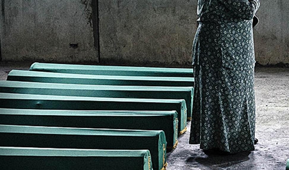 Families die hun doden kwamen begraven, moesten door rijen jouwende Serviërs lopen