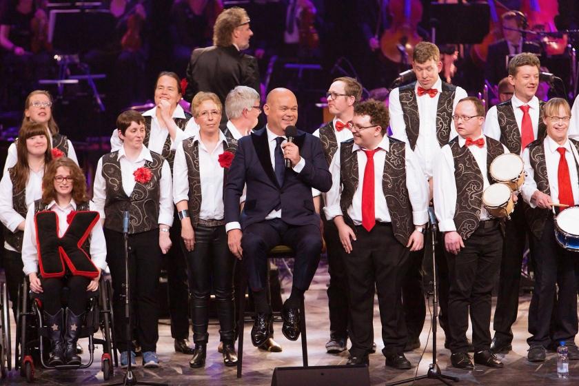 Leden van het APK-koor op het podium van theater Carré tijdens het Knoop Gala afgelopen zaterdag, met presentator Paul de Leeuw. APK staat voor Alkmaars Prachtkoor.  (ntr)