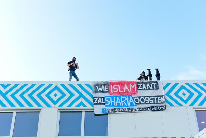 Twee mannnen hingen maandag een spandoek aan de gevel van de nieuwe islamitische middelbare school in Amsterdam.  (anp / ginopress)