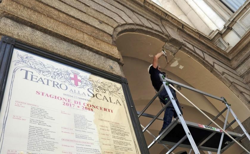 Een man voert controles uit aan een van de bogen van het Teatro alla Scala in Milaan, nadat geconstateerd was dat hier en daar stukken pleisterwerk waren losgeraakt.  (epa / Matteo Bazzi)