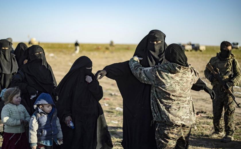 Leden van de Koerdische SDF fouilleren Syrische vrouwen en kinderen die wegtrekken uit Baghouz, de laatste enclave van de terreurorganisatie ISIS in Syrië.  (afp / Delil Souleiman en anp / Remko de Waal)