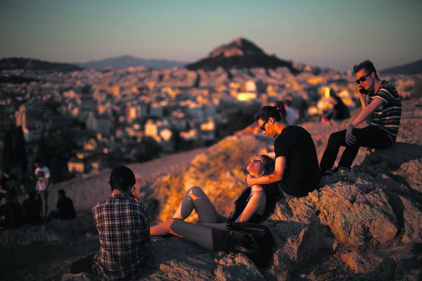 Griekse jongeren kijken uit over Athene. Veel jonge Grieken verlaten het land, anderen proberen vernieuwende bedrijfjes op te zetten.  (ap / Emillio Morenatti)