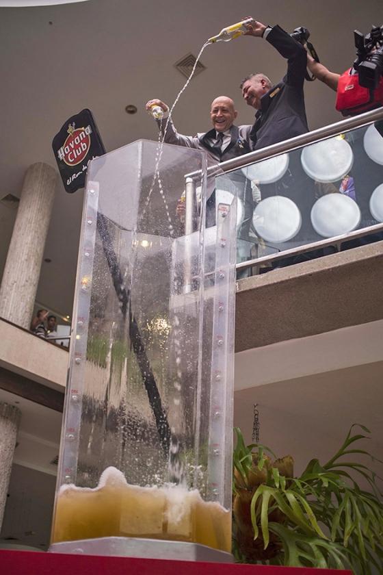 Barmannen vullen een gigantisch glas met rum voor een wereldrecordpoging Cuba Libre maken in Havane. De Cubaanse 'supercocktail' bevatte onder andere 192 flessen rum en 350 liter frisdrank.  (ap / Desmond Boylan)