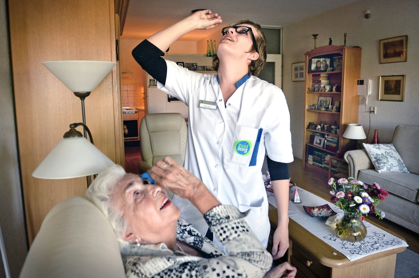 Een medewerker van Zuidzorg leert een cliënt hoe ze voortaan zelf haar oogdruppels kan nemen.  (Marcel van den Bergh)