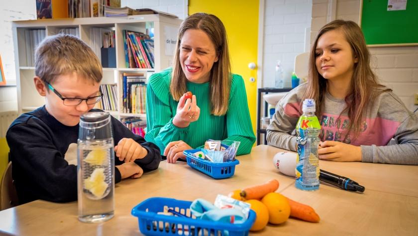 Minister Carola Schouten van Landbouw, Natuur en Voedselkwaliteit deelt fruit uit op basisschool De Springbok in Den Haag.  (anp / Lex van Lieshout)