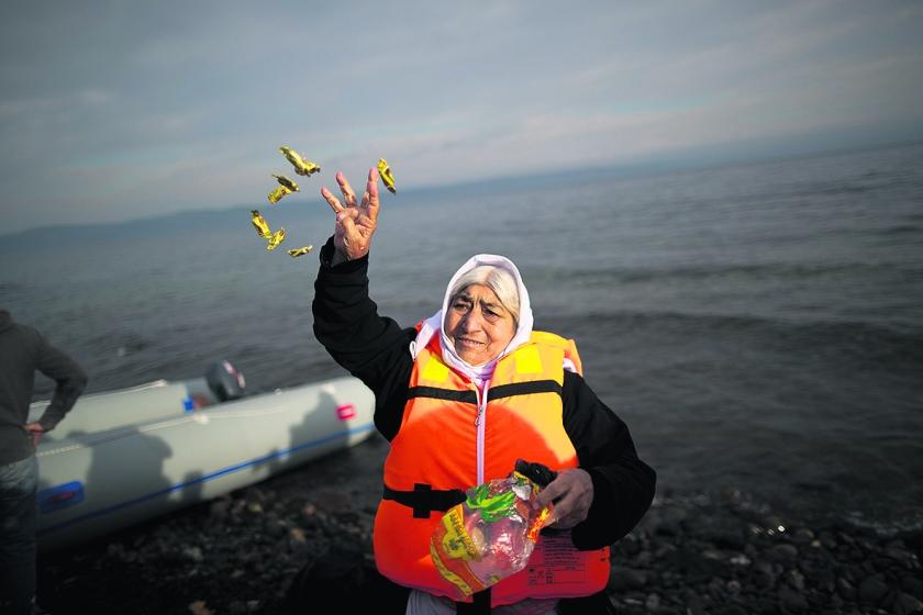 Een vluchteling strooit met snoepjes bij aankomst op het Griekse eiland Lesbos.  (ap / Muhammed Muheisen)