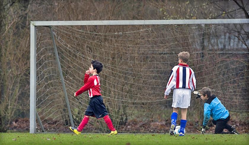 Snel geleerd. Een pupil van voetbalclub PSV heeft gescoord en legt iedereen het zwijgen op.  (Klaas Jan van der Weij)