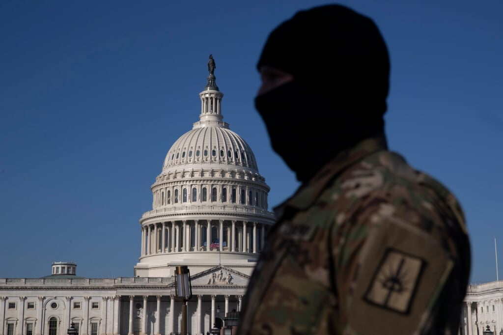 2021-01-12 09:35:43 epa08933147 A member of the US National Guard stands on the grounds of the East Front of the US Capitol in Washington, DC, USA, 12 January 2021. At least ten thousand troops of the National Guard will be deployed in Washington by the end of the week, with the possibility of five thousand more, to help secure the Capitol area ahead of more potentially violent unrest in the days leading up to the Inauguration of US President-elect Biden. Democrats are attempting to impeach incumbent US President Trump after he incited a mob of his supporters to riot on the US Capitol in an attempt to thwart Congress from certifying Biden's election victory.  EPA/MICHAEL REYNOLDS  (beeld Epa/michael Reynolds)