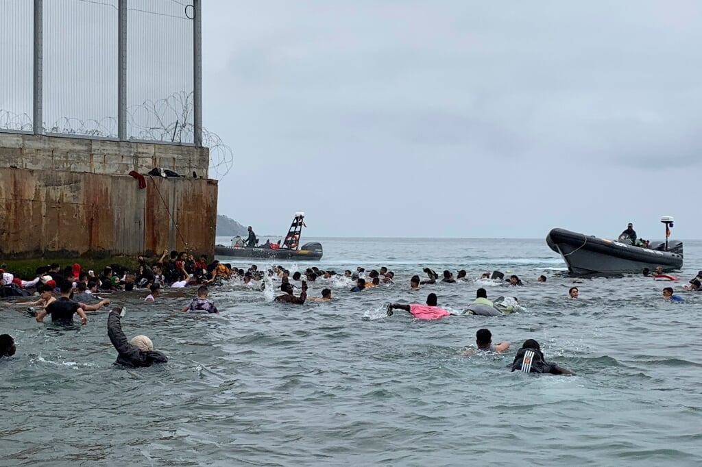 2021-05-18 06:33:41 epa09208440 Hundreds of people try to swim from Fnideq (Morocco) to Ceuta, Spanish enclave in the north frica, 18 May 2021, as Spanish army troops are deployed after a total of 5,000 Moroccan nationals managed to entry the city by sea during the night and hundreds continue to arrive.  EPA/MOHAMED SIALI  (beeld Epa/mohamed Siali)
