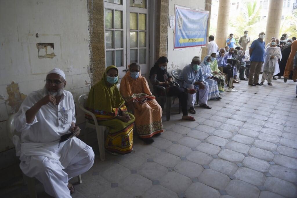 Inwoners van Karachi (Pakistan) wachten om gevaccineerd te worden tegen het coronavirus. Het land ging vorige week in complete lockdown. Geld storten op Giro555 om sneller te vaccineren in deze landen is niet echt solidair.  (beeld afp / Rizwan Tabassum)