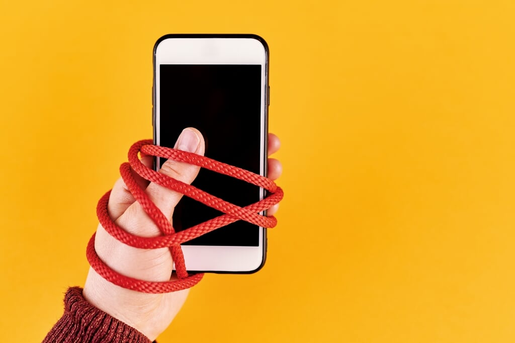 Social media dependency. Woman holding and touching smart phone.  (beeld istock)