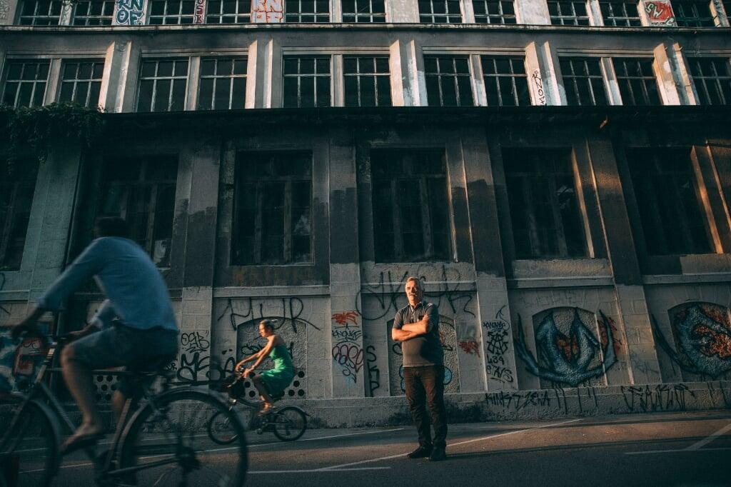 SLOVENIE Verhaal over de uitgewisten (Rosa van Gool) - Op de foto: Irfan Beširevic, in de achtergrond ROG, een oude fabriek en voormalig cultureel centrum  (beeld Marlena Waldthausen)