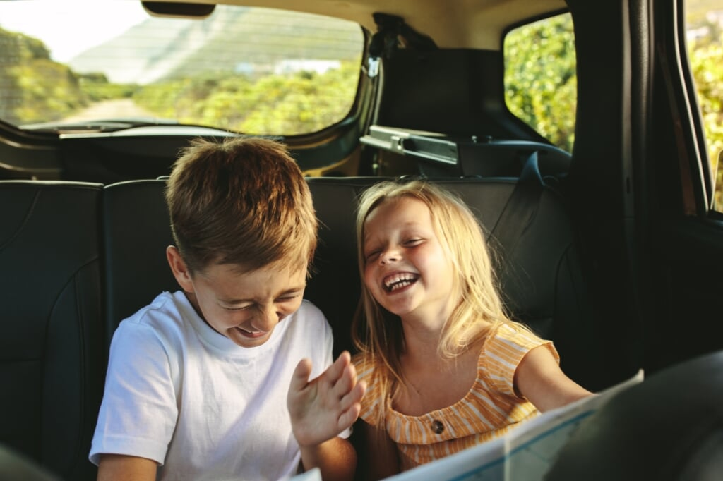 Small boy and girl sitting on backseat of car looking at map and smiling. Kids traveling in a car on roadtrip playing with a map. (Small boy and girl sitting on backseat of car looking at map and smiling. Kids traveling in a car on roadtrip playing wi  (beeld istock)