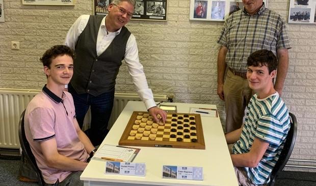 <p>Wethouder Mark Pater met de eerste zet op het bord van titelverdediger Machiel Weistra (links).</p>