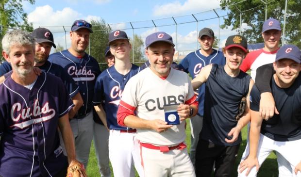 <p>Martijn Hartgerink (midden) van de Hardenberg Cubs toont de eremedaille van de KNBSB, die hij kreeg als dank voor zijn inzet voor de vereniging en de honkbalsport. </p>