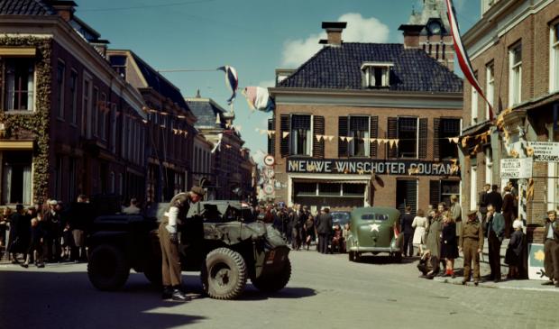 Canadese militairen en feestvierders in de Langestraat in Winschoten, voorjaar 1945. Fotograaf onbekend, collectie National Archives of Canada.