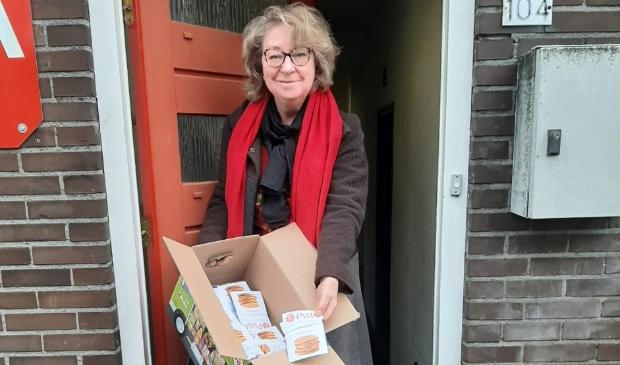 <p>PvdA-fractievoorzitter Thea van der Veen neemt dozen met kanjerkoeken in ontvangst om ze later uit te delen.</p>