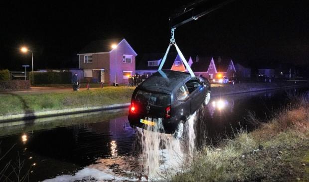 <p>De auto wordt uit het kanaal getakeld (foto Van Oost Media).</p>