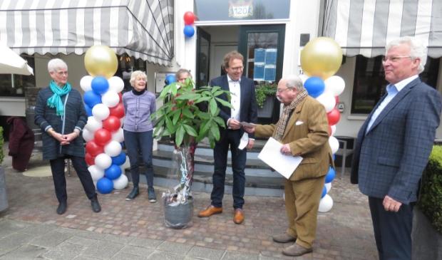 <p>Maarten Rietveldt biedt, terwijl het bestuur van het Nut toekijkt, Frank Faber een grote plant plus een envelop aan.</p>