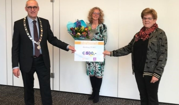 Burgemeester Hoogendoorn en Adriana Jaarsma (midden) reiken de prijs uit aan één van de winnaars, Ina Slagter van Stichting POSO.