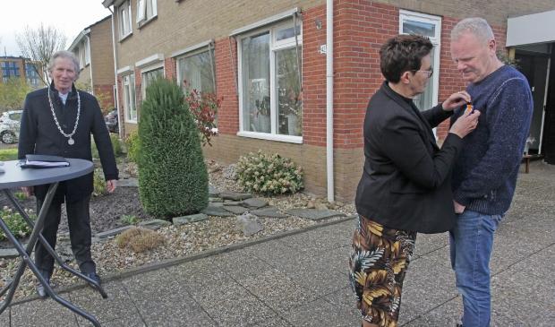 <p>Onder toeziend oog van burgemeester Sipke Swierstra krijgt Bram Vazel de onderscheiding opgespeld &nbsp;door zijn vrouw Jopie. Foto: Bert Woltjes.&nbsp;</p>