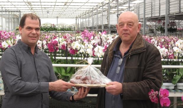 Directeur Piet Aardse van Aardse Orchids (links) ontvangt namens het bestuur van ZNC een worstplankje.